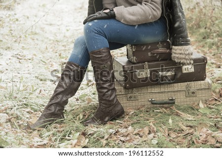 Idea of Big travel Stylish slim woman waiting for something on three retro old  suitcases Copy space for inscription Girl sit on leather case on grass, autumn leaves and snowflakes background