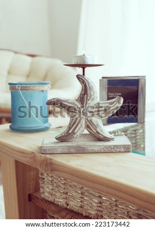 Idea of interior decor in beach cottage style with trendy glass candlestick and rustic photo frame. - stock photo