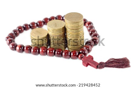 Idea of religion as successful business - rosary with coins - stock photo