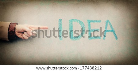 Idea written on wall with a chalk and hand pointing at sign. - stock photo