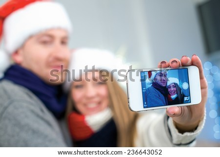 Ideal Christmas photo. Young and beautiful couple wearing Santa Claus hats is making photo of themself on mobile phone in festive Christmas decorated living room - stock photo