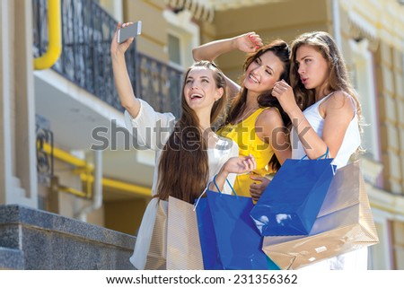 Ideal mobile photo while shopping. Three young and pretty girls are standing with shopping bags and taking photos on mobile phone. All are smiling and having great fun - stock photo