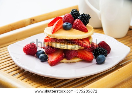Ideal Sunday morning treat - brunch - delicious pancakes with fresh fruits. - stock photo