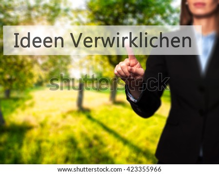 Ideen Verwirklichen ( Realize Ideas in German) - Businesswoman hand pressing button on touch screen interface. Business, technology, internet concept. Stock Photo - stock photo