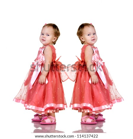 Identical twin baby girls  in an elegant pink dress isolated on white background.