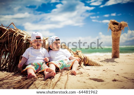 identical twin boys relaxing on tropical beach - stock photo