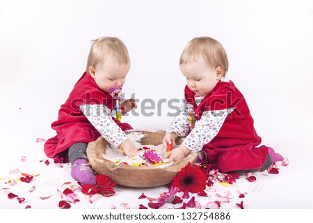 identical twin sisters playing with a wooden bowl of sand, rose and gerbera petals. - stock photo