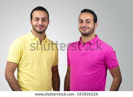 Identical twins portraits shot against white background - stock photo