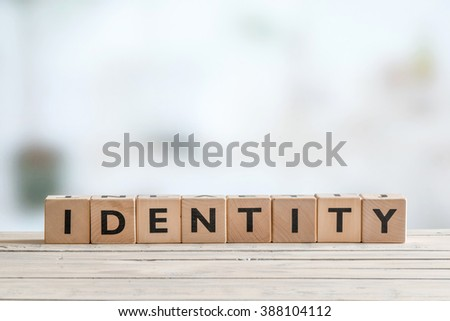 Identity sign made of cubes on wooden table - stock photo