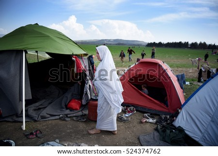 Idomeni, Greece - March 2, 2016. A refugee woman walks outside a tent at the makeshift refugee camp of Idomeni, at the Greek - Macedonian border.