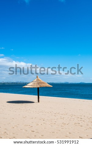 Idyllic beach resort with pristine white sand, blue water, blue skies, beach chairs and natural sun shelter