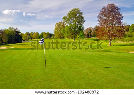 Idyllic golf course scenery with flag - stock photo