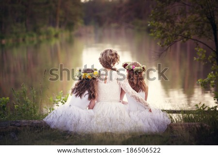 Idyllic landscape mom with daughters sitting at the edge of the lake and watched the water with his back to the camera, all dressed in white lace dresses. - stock photo