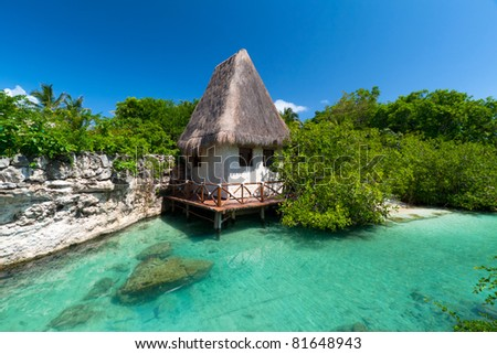 Idyllic mexican jungle scenery with hut on the water - stock photo