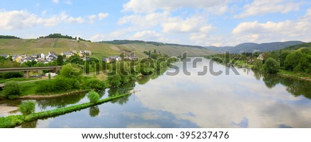 idyllic moselle river at springtime, with hillside vineyards - stock photo