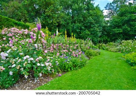 Idyllic pretty English country formal garden, in full bloom - stock photo