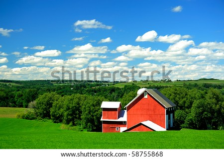 idyllic red barn and green pastures in open land new york state