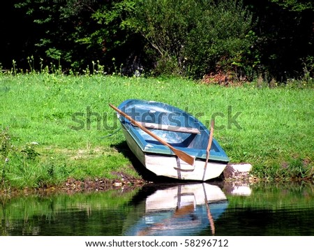 Idyllic rowing boat on a lake in the alps - stock photo