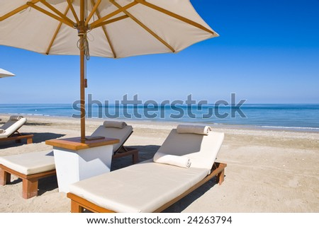 Idyllic scene of deck chairs under an umbrella on a clean beach in the hot afternoon sun. - stock photo