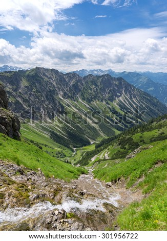 Idyllic stream in a steep mountain landscape, taken in the Bavarian Alps, Germany, in vertical format.   - stock photo