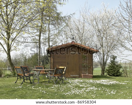idyllic summerhouse and garden furniture at spring time - stock photo