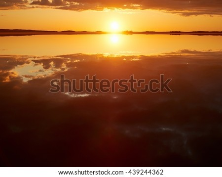 Idyllic sunset with some clouds in summer. Dramatic reflection of the Sun in the still water of a lake in Finland. - stock photo