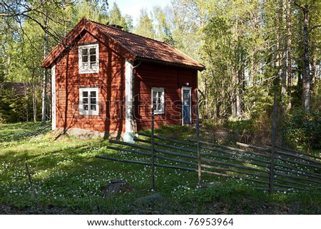 Idyllic Swedish house in a forest with old fence. Typical old wooden, painted red and white. - stock photo