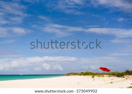 Idyllic tropical beach with red umbrella, pink sand, turquoise ocean water and blue sky at deserted island in Caribbean - stock photo