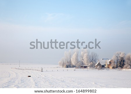 idyllic winter landscape in Thuringia with a rural property - stock photo