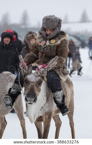Iengra, Neryungri District, Yakutia, Russia. 5 March 2016. The Evenk girl in national clothes riding a reindeer during the celebration of the reindeer herders - stock photo