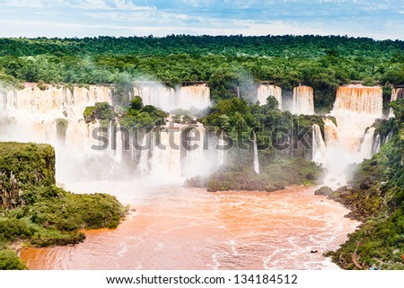Iguazu falls, one of the new seven wonders of nature. UNESCO World Heritage site. View from the brazilian side showing the argentinean side, during rains season with brown water. - stock photo