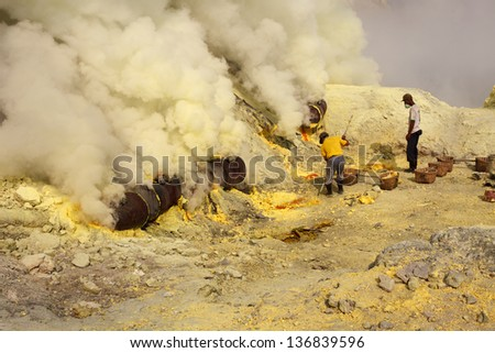 Ijen volcano crater, people working in sulfur mining industry - stock photo