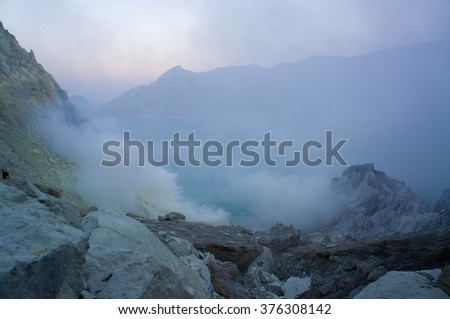 Ijen volcano in East Java contains the world's largest acidic volcanic crater lake, called Kawah Ijen, spewing out sulphur smoke in the morning  - stock photo