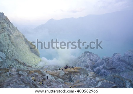 Ijen volcano in East Java contains the world's largest acidic volcanic crater lake, called Kawah Ijen, spewing out sulphur smoke in the morning. Sun is hidden in mist. - stock photo