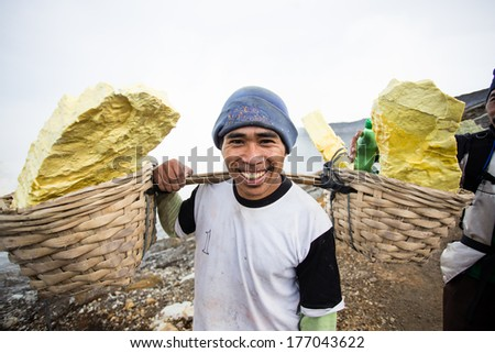IJEN VOLCANO, INDONESIA - FEB 15:Worker carries sulfur inside crater on Febuary 15, 2014 in Ijen Volcano, Indonesia. He carries the load of around 80kg to the top of the crater and then 3km down.  - stock photo