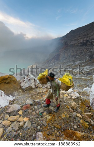 IJEN VOLCANO, INDONESIA - FEB 9: Worker carrying sulfur inside Ijen crater on Feb 9, 2014 in East Java, Indonesia. He carries the load of around 90kg to the top of the rip and then 3 km down.