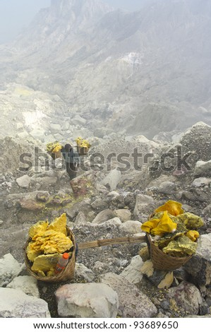IJEN VOLCANO, INDONESIA - JAN 10: Worker carrying sulfur inside Ijen crater on January 10, 2011 in Ijen Volcano, Indonesia. He carries the load of around 60kg to the top  and then 3km down. - stock photo