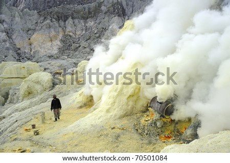 IJEN VOLCANO, INDONESIA - JUNE 29: Worker extract the sulfur from active volcano on June 29, 2010 in East Java, Indonesia. They do this with min.protection,and gases make it hard to breathe. - stock photo