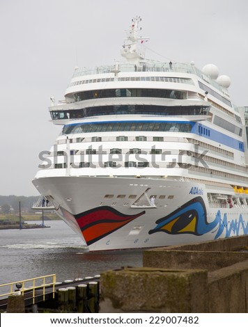 IJMUIDEN, THE NETHERLANDS - JULY 30, 2013: Cruise ship AIDA arrives at lock at IJmuiden, The Netherlands. Cruise ship AIDA is famous for the paintings of eyes and lips. - stock photo