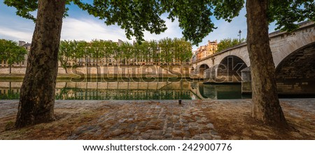 Ile Saint Louis and Pont Marie with the Seine River banks lined with aspen trees on a quiet early morning in the middle of the summer, Paris 4th arrondissement, France. - stock photo