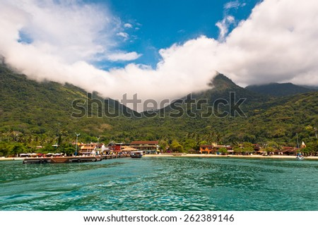 ILHA GRANDE, BRAZIL - OCTOBER 18, 2013: Vila do Abraao town view from the sea with beautiful landscape. Located in Ilha Grande island near Rio de Janeiro, it is a perfect getaway from busy city life. - stock photo