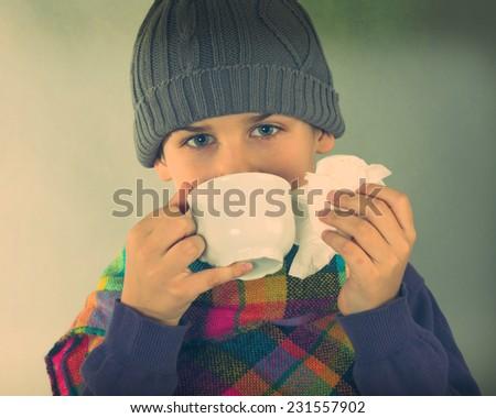 ill boy drinking hot tea - stock photo