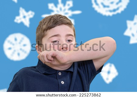 Ill child covering his mouth with his arm to contain sneeze - stock photo