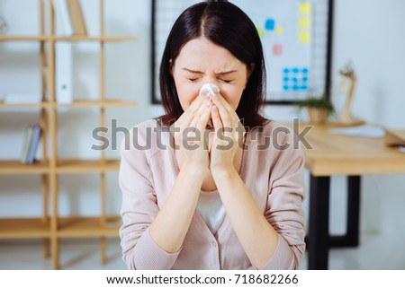 Ill female person sneezing at work