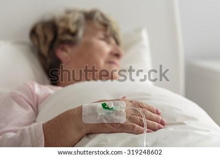 Ill female retiree lying in hospital bed - stock photo