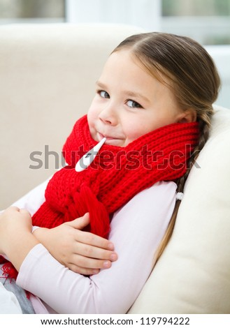 Ill little girl is laying on sofa with thermometer in her mouth - stock photo