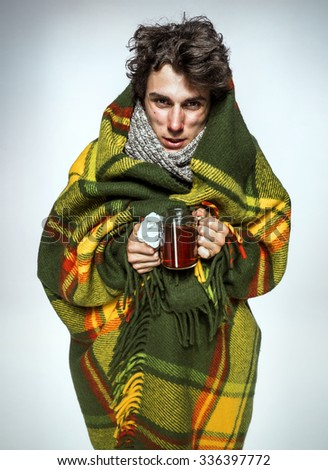 Ill Man covered with plaid blanket with hot tea/ sick man suffering cold and winter flu virus. Medication or drugs abuse, healthcare concept - stock photo