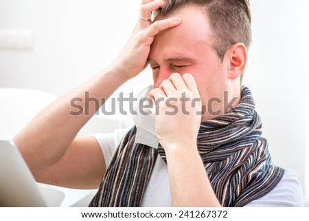 Ill man suffering from rhinitis sitting on the couch at home. Strong headache - stock photo