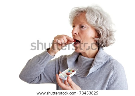 Ill old woman taking a pill from a pill dispenser - stock photo