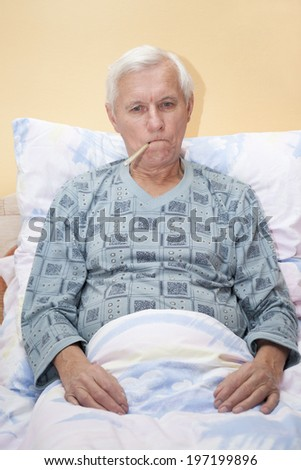 Ill senior man checking temperature with thermometer in bed. - stock photo